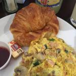 Omelette with very flaky croissant and berry jam