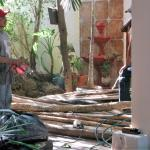 Workers in the process of building a palapa near the pool