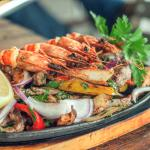 Sizzling Ultimate Fajita: onion, pepper, chicken, strip steak & king prawns- with all the trimmi