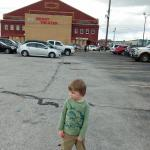 The young nephew in front of the Brady Theater in the parking lot.