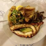 Fried octopus with boiled potatoes, vegetables and salad