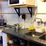 Microondas incluido. Varias tazas y vasos, todo limpio y ordenado.