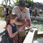 Brian handing our daughter a turtle to hold at the Turtle farm.