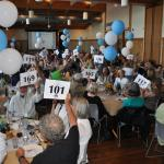 A packed house (144ppl) raise their bid cards for the NWSWB at the NWMC