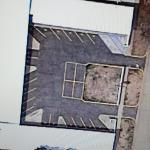 Arial photo.  Small parking lot with low brick wall between entrance/exit.  Truck/trailer won't