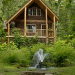 The Squirrel's Den cabin overlooks a pond with a waterfall.