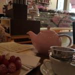 Tea and raspberry tarte with chocolate counter as a backdrop