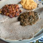 Injera, an Ethiopian sourdough plate, with lentils, beans and collard greens