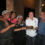 Jana, chef, and staff giving Trevor his cake