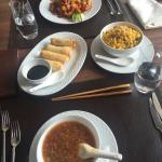 Tasty and crispy spring rolls, side of fried corn combinatoon, soup and tasty chicken with peanu