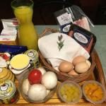 Our breakfast basket with bacon, sausages, mushrooms, tomato, bread, butter, condiments and more