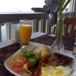 Breakfast of bacon, grilled fish , fried egg, salad and bread