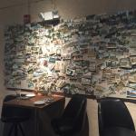 Picture of restaurant from the bar and a wall full of postcards.