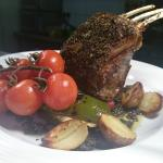Herb-crusted rack of lamb with Provencale vegetables, roast new potatoes and black olive tapenad