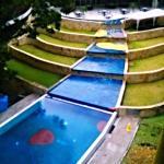 Vista de la piscina y al fondo el restaurante con su terraza