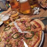 Pizza vegana y jarras de cerveza bien fresca