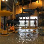 There are large slides and water fountains inside the pool area.