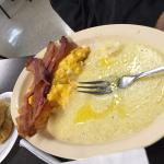 Cheesy eggs with grits and bacon and a bisquit
