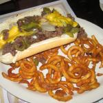 The delicious cheese steak sandwich with curly fries