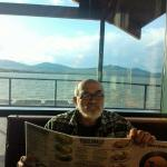 My husband seated at booth in the restaurant with lake view behind him.