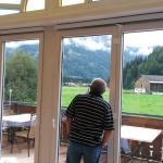Blick aus dem Speisesaal auf die Terrasse, die Wiesen und Berge