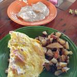 Ham and cheese omelet with home fries and biscuit with gravy.