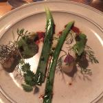 Young garlic with herbs, syrup from carrots. Unripe black currant berries