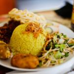 on photo, is a yellow rice(nasi kuning),with urap(vegetable mix salad) krupuk,perkedel kentang,e