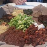 4 dinners served family style on top of injera with salad in the middle