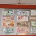 A collection of foreign bills posted high on the walls