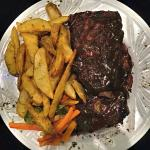Full rack of pork ribs served with potato wedges