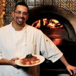 Executive Chef, Marc Albino, standing in front of the imported Italian pizza oven.