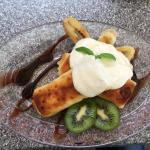 Sweet and tasty crepes with farmer's cheese and sour cream served with fruit