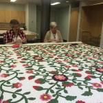 Volunteers at the IQSCM sew a sleeve on this 19th-century red & green appliqué quilt, for exhibi