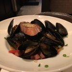 Mussels appetizer in beer with ham, onions and tomatoes, delicious