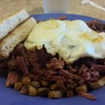 Roast beef hash over home fries topped with eggs and toast