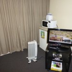Tv, microwave, fridge, toaster, and hot water pot in rooms