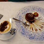 Chocolate cake with ice cream inside and cappucino
