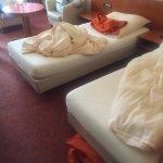 alte braune Möbel, lila Teppich und Vorhänge und orangefarbene Tagesdecken