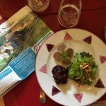 Saucisson de canard, oignons grelots mijotés au vin rouge, salade aux pignons grillés
