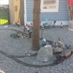 "The electric train set in the front yard. Note the ""Godzilla"" figurine just left of the train!"