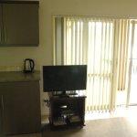 kitchenette, tv, baie vitrée et porte entrée