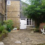 Dog friendly accom is built on the side of the house, there is this patio then a large garden