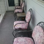 front two chairs have ripped fabric on dirty porch overlooking pool