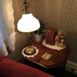 sofa corner side table and lamp, lace curtains on window
