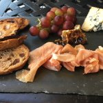 Prosciutto and blue cheese served with honey, grapes and toasted bread