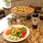 One of our fabulous pizzas with house salad, paired with some premium wine