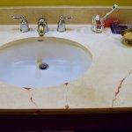 Bathroom vanity broken in 4 places. Shoddy repair with red putty