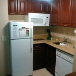 Kitchen including full fridge/freezer, dishwasher, countertop range, microwave, dishes and cutle