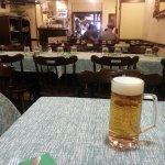 Il tavolo apparecchiato con la birra e l'interno del locale